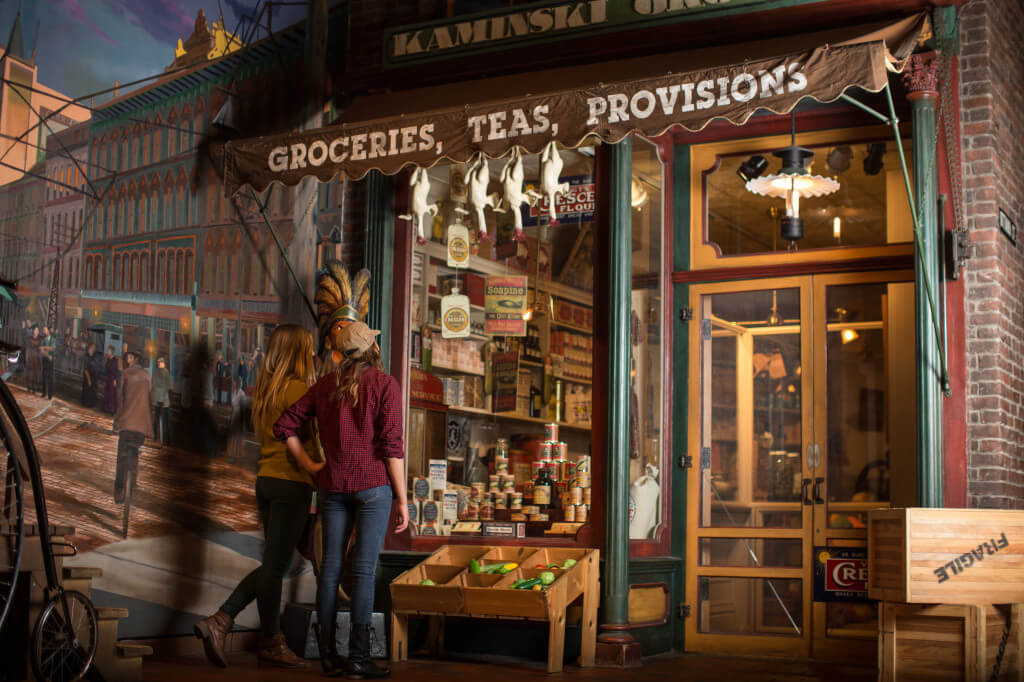 Visitors looking at grocery store in the Streets of Old Grand Rapids exhibit