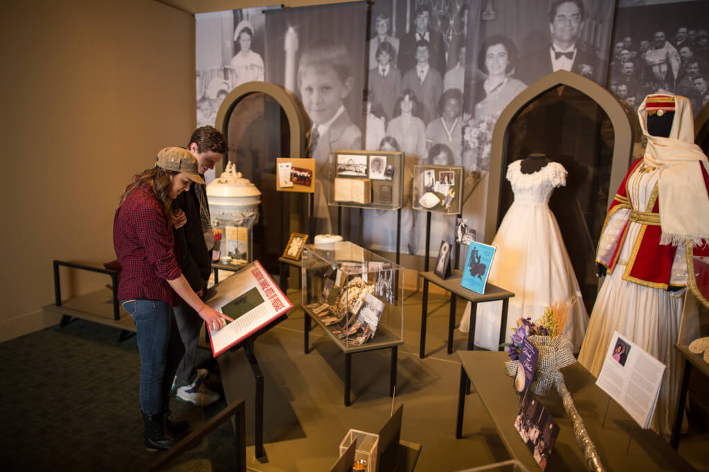 Visitors exploring cultural artifacts in Newcomers: The People of This Place exhibit