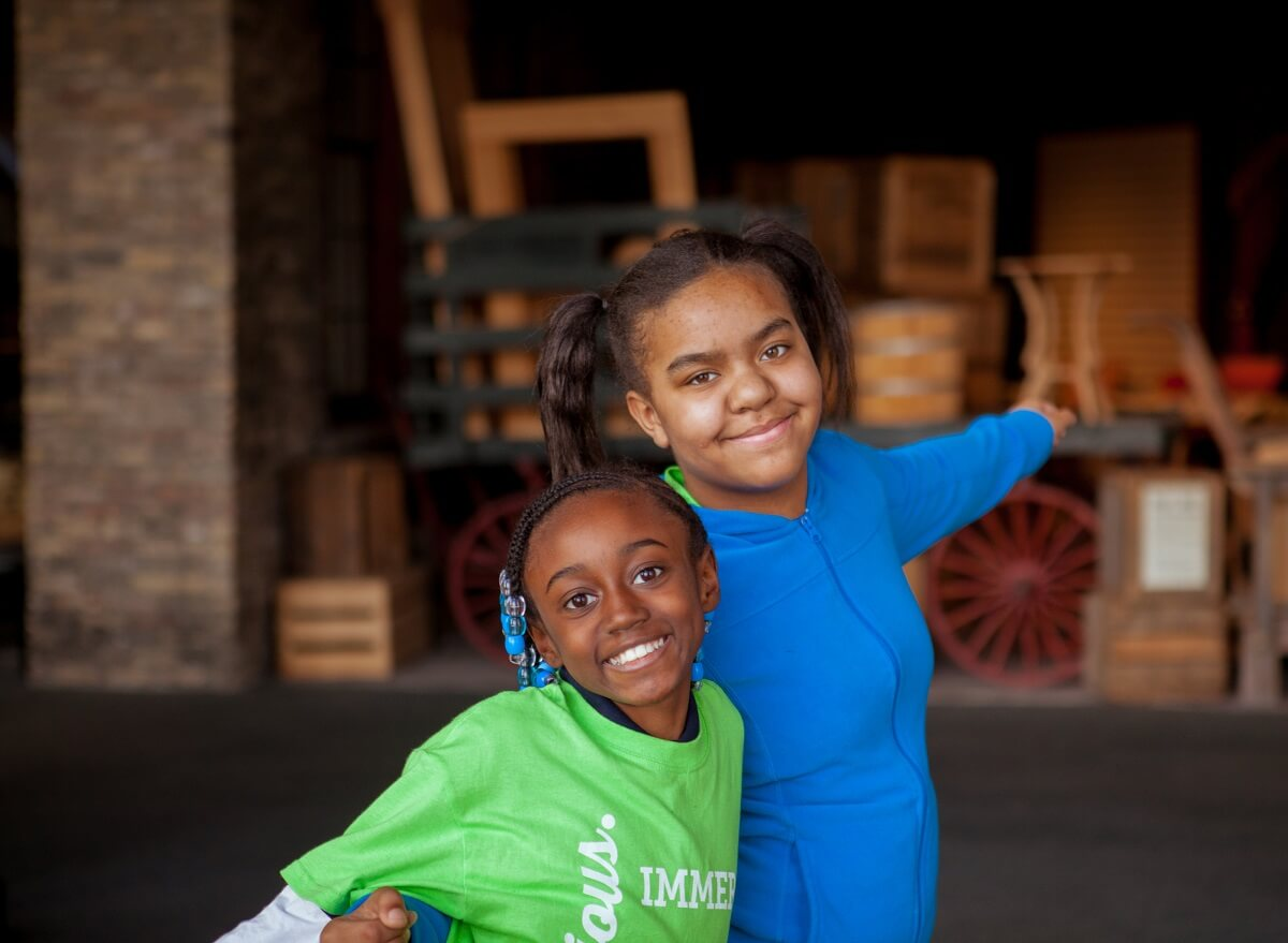Young girls in Immerse program smile for a photo
