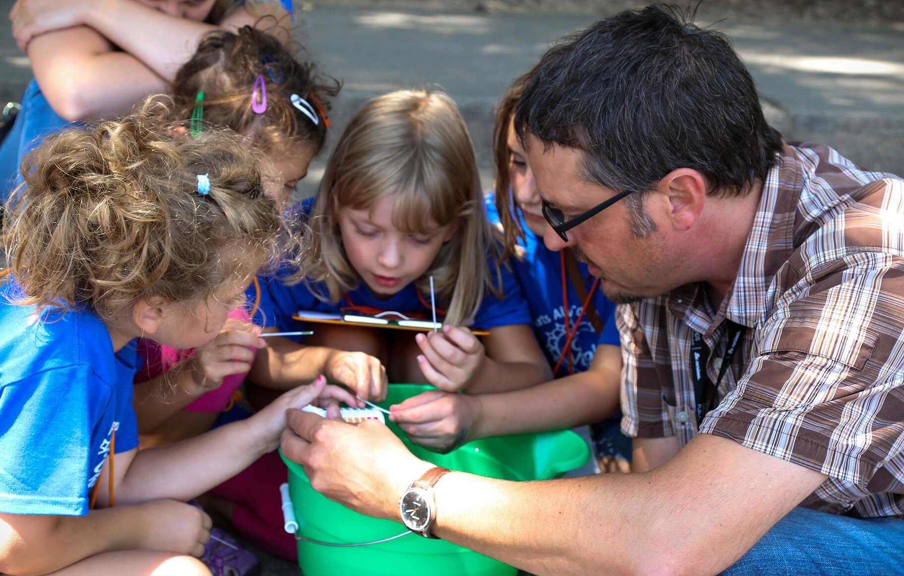 Educator with kids testing water quality of the river through water gathered in a bucket