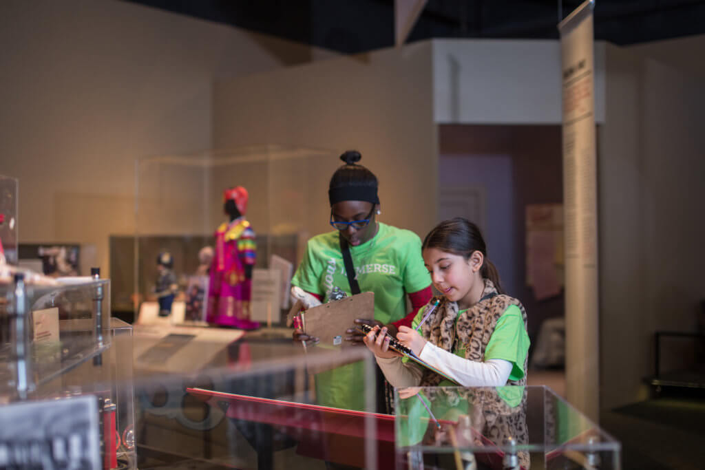 Students take notes in Newcomers - The People of This Place exhibit
