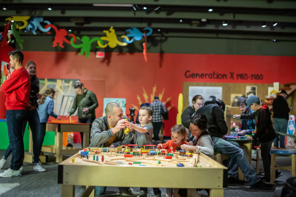 Parents play with young kids in Toys exhibit