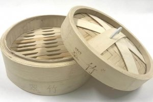 Asian rice steamer made of bamboo and features writing around the sides
