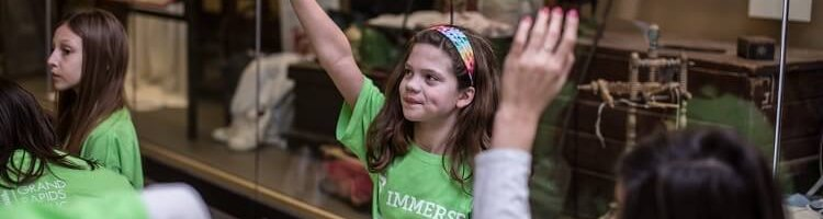 Immerse student raises hand in exhibit program