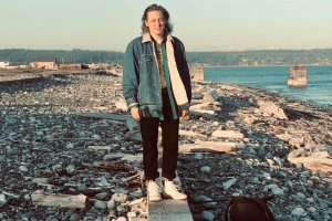 Seth Beck, a concerts under the stars artist, stands on wood on rocky beach